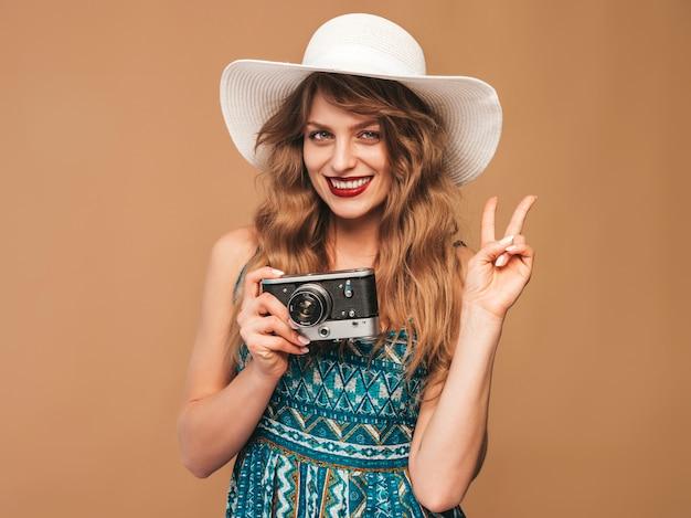 Porträt der netten lächelnden jungen frau, die foto mit inspiration macht und sommerkleid trägt. mädchen, das retro- kamera anhält. model posiert in hut