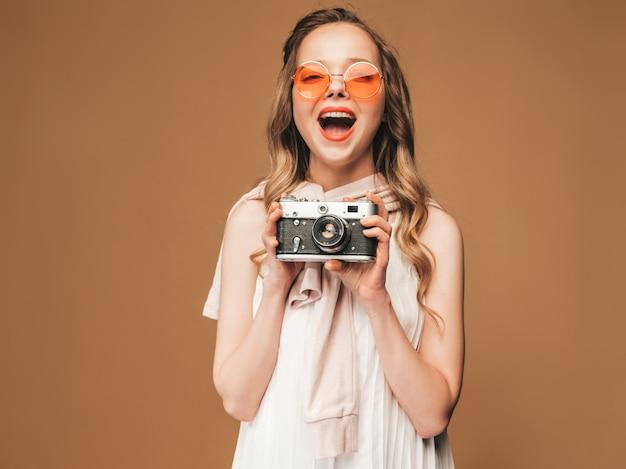 Porträt der netten lächelnden jungen frau, die foto mit inspiration macht und weißes kleid trägt. mädchen, das retro- kamera anhält. modell bei der sonnenbrilleaufstellung