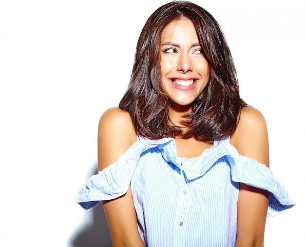 Porträt der netten lächelnden modefrau, die im zufälligen blauen hippie-sommer verrückt geht, kleidet ohne make-up auf weißer wand