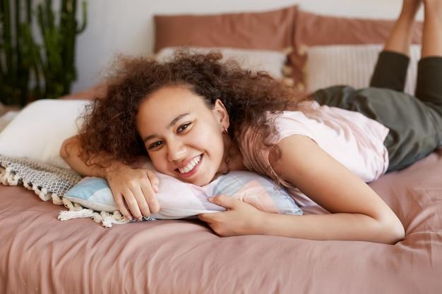 Porträt der netten lockigen afroamerikanischen jungen frau, die auf dem bett liegt, den sonnigen tag zu hause genießt, breit lächelt und glücklich aussieht.