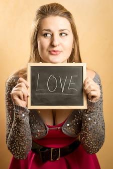Porträt der netten lustigen frau, die tafel mit wort liebe hält