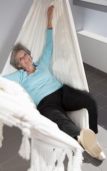 Porträt der netten pensionierten frau, die in der hängematte auf balkon stillsteht
