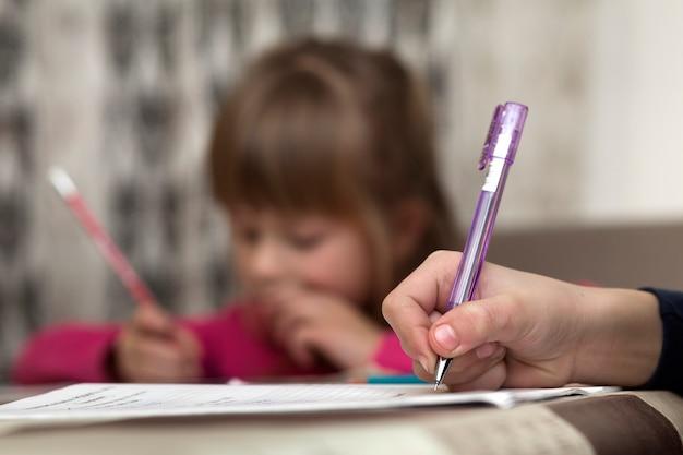 Porträt der netten recht kleinen ernsten kindermädchenzeichnung mit bleistift auf papier auf unscharfer oberfläche. kunsterziehung, kreativität, hausaufgaben machen und kinderaktivitätskonzept.