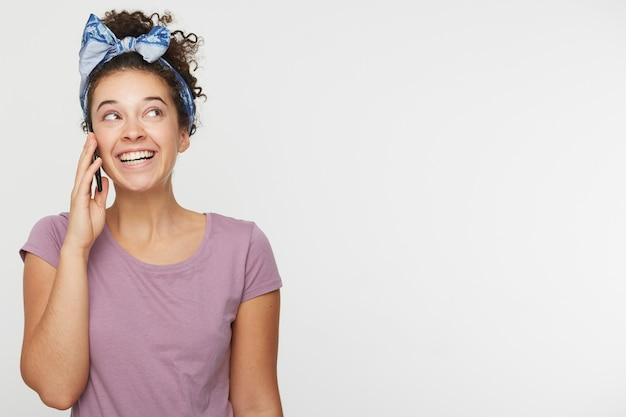 Porträt der netten reizenden attraktiven brünetten frau mit dem lockigen haar im lässigen t-shirt und im stirnband, die mit jemandem sprechen, der etwas besonderes am telefon ist