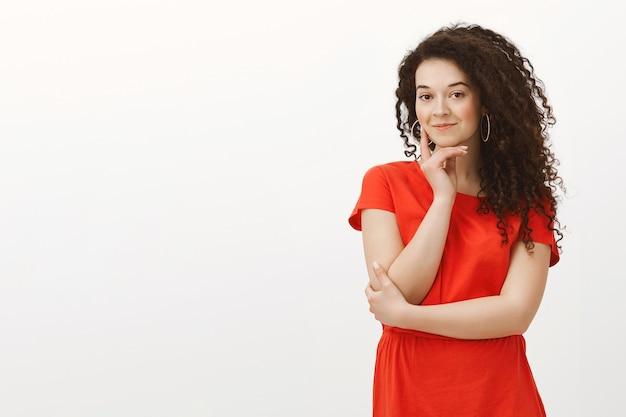 Porträt der neugierigen bezaubernden studentin im modischen roten kleid