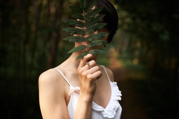 Porträt der nicht wiedererkennbaren mysteriösen jungen frau, die weißes riemenkleid trägt, das im wald allein das gesicht mit großem farnblatt bedeckend aufwirft