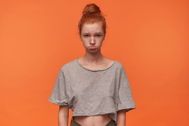 Porträt der niedlichen beleidigten jungen rothaarigen frau mit brötchenfrisur, die lässige kleidung trägt, über orange hintergrund mit händen nach unten posierend, faltige stirn mit gespitzten lippen