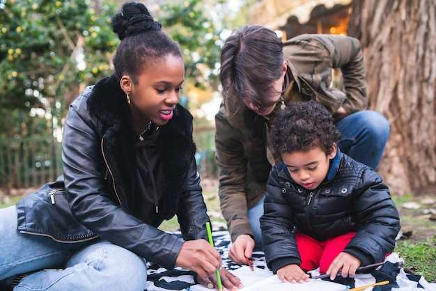 Porträt der niedlichen gemischten ethnischen familie, die eine gute zeit zusammen im park draußen hat.