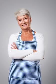 Porträt der niedlichen großmutter, die schürze trägt