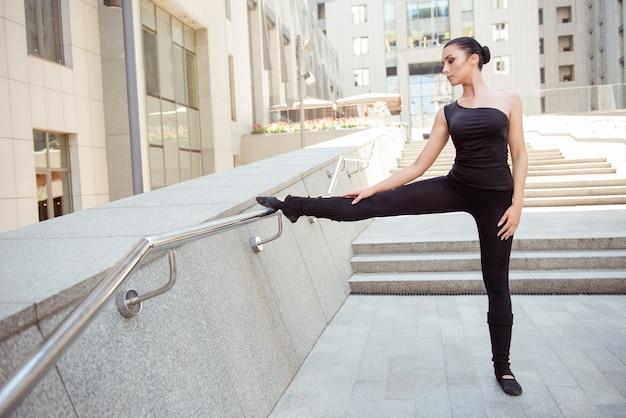 Porträt der niedlichen jungen ballerina, die am geländer steht