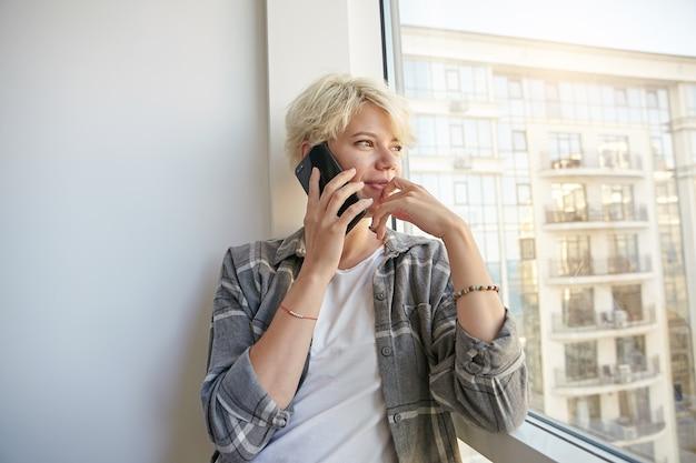 Porträt der niedlichen jungen frau mit kurzem haarschnitt, die am fenster steht und nachdenklich auf die straße schaut, das telefon in der hand hält und ihr gesicht berührt