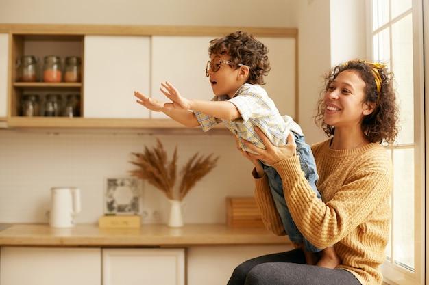Porträt der niedlichen jungen lateinamerikanischen frau im pullover, der auf wndowsill sitzt und ihren zweijährigen sohn hält, der hände ausstreckt, als ob fliegen. glückliche mutter und kind spielen im gemütlichen kücheninnenraum