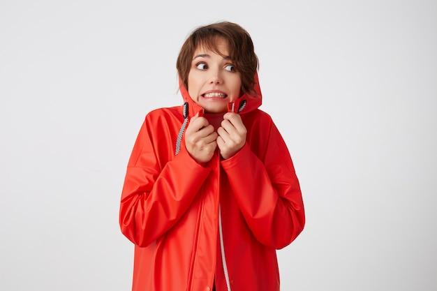 Porträt der niedlichen jungen verängstigten kurzhaarigen frau im roten regenmantel, runzelt die stirn und fürchtet, nach rechts zu schauen, fühlt sich kalt an, versteckt sich in der kapuze. stehen.
