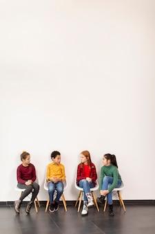 Porträt der niedlichen kleinen kinder in den jeans, die in stühlen gegen die weiße wand sitzen