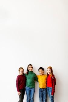 Porträt der niedlichen kleinen kinder in den jeans, die kamera betrachten und lächeln, die gegen die weiße wand stehen