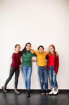 Porträt der niedlichen kleinen kinder in den jeans, die vorne schauen und lächeln, gegen die weiße wand stehen