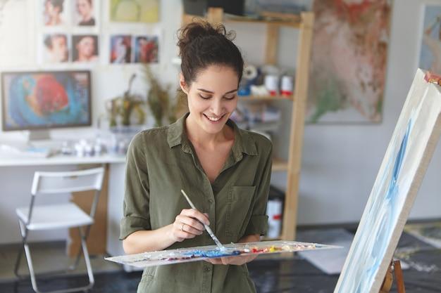 Porträt der niedlichen künstlerin, die in der werkstatt arbeitet, mit pinsel und aquarellen malt, in der nähe der staffelei steht und froh ist, sich ihrem hobby zu widmen. talentierter junger maler, der bild zeichnet