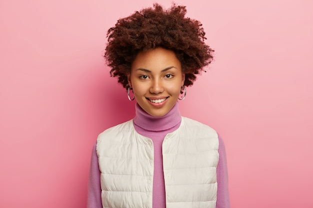 Porträt der niedlichen lockigen frau hat natürliche schönheit, lächelt angenehm, trägt ohrringe, weiße weste, drückt freude aus, posiert vor rosa hintergrund.