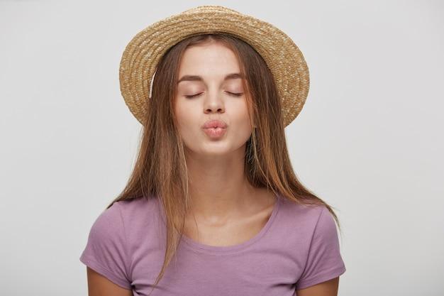 Porträt der niedlichen reizenden frau im lässigen outfit in einem strohhut mit einem rosa band, das blasenden kuss sendet