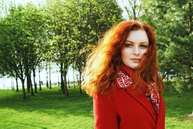 Porträt der niedlichen rothaarigen frau in einem roten mantel im park