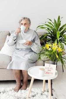 Porträt der oma, die kaffeetasse genießt