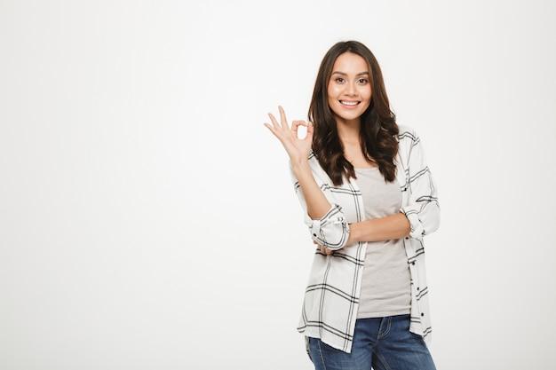 Porträt der optimistischen erfüllten frau mit dem langen braunen haar, das auf kamera aufwirft und das okayzeichen lokalisiert über weiß zeigt