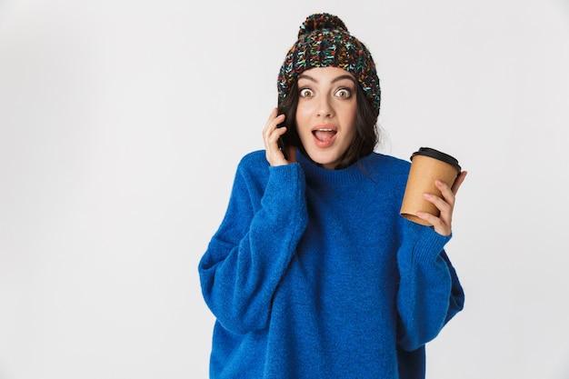 Porträt der optimistischen frau, die wintermütze trägt, die auf handy spricht und kaffee zum mitnehmen trinkt, während sie steht, lokalisiert auf weiß
