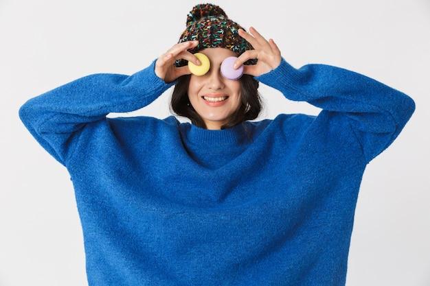 Porträt der optimistischen frau, die wintermütze trägt, die macaronplätzchen im stehen hält, lokalisiert auf weiß