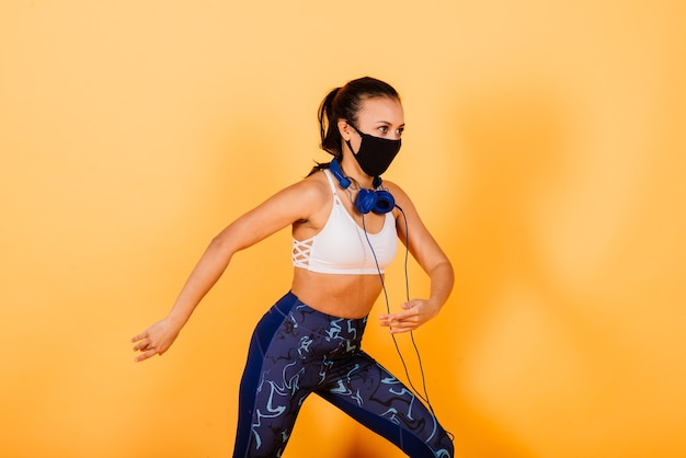 Porträt der passenden afrikanischen frau, die gesichtsmaske trägt. sportliche frau in der fitnesskleidung, die auf einem gelben hintergrund steht.
