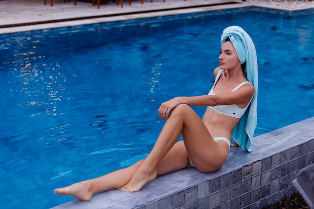 Porträt der passenden schlanken jungen kaukasischen frau im blauen bikini außerhalb der villa durch schwimmbad am regnerischen tag