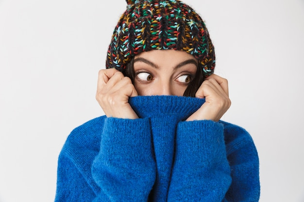 Porträt der positiven frau, die wintermütze lächelt, während sie steht, lokalisiert auf weiß