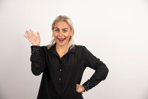 Porträt der positiven frau im schwarzen hemd, das auf weißem hintergrund aufwirft. hochwertiges foto