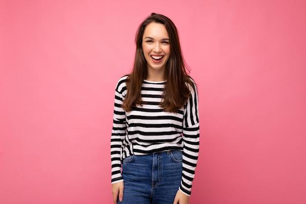 Porträt der positiven fröhlichen modischen frau in der freizeitkleidung lokalisiert auf rosa hintergrund mit