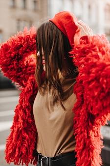 Porträt der positiven glatthaarigen frau gekleidet in zotteligem pelzmantel, t-shirt und baskenmütze gegen hintergrund des gebäudes.