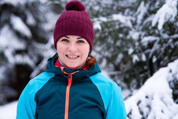 Porträt der positiven glücklichen jungen schönen frau, die in einem verschneiten winterwald lächelt