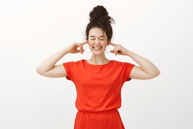 Porträt der positiven gutaussehenden frau im roten kleid, breit lächelnd und ohren mit zeigefingern bedeckend