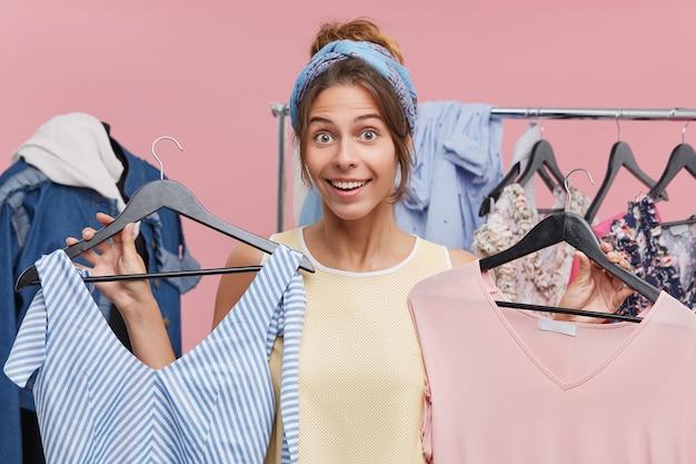 Porträt der positiven hübschen frau, die kleiderbügel mit kleidern hält, die zwischen zwei herrlichen kleidern wählen und auf ihren rat warten. weiblicher shopaholic genießt das einkaufen im verkauf und kauft neues kleidungsstück