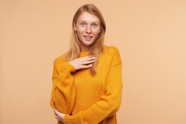 Porträt der positiven jungen reizenden rothaarigen frau, die erhabene handfläche auf ihrer brust hält und gemütlichen strickpullover trägt, während sie auf beige posiert