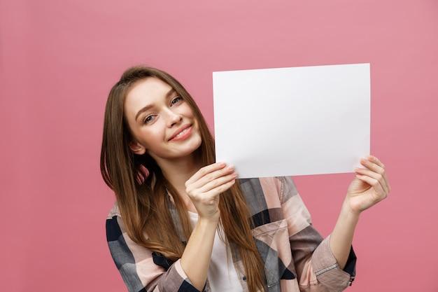 Porträt der positiven lachenden frau, die weißes großes modellplakat lächelt und hält