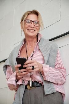 Porträt der positiven modischen reifen geschäftsfrau mit anhänger, der smartphone verwendet, um geschäftliche probleme zu lösen