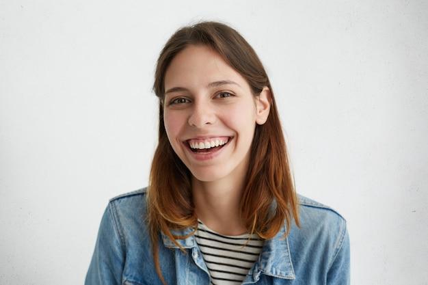 Porträt der positiven natürlichen frau mit dunklem haar in der jeansjacke breit lächelnd
