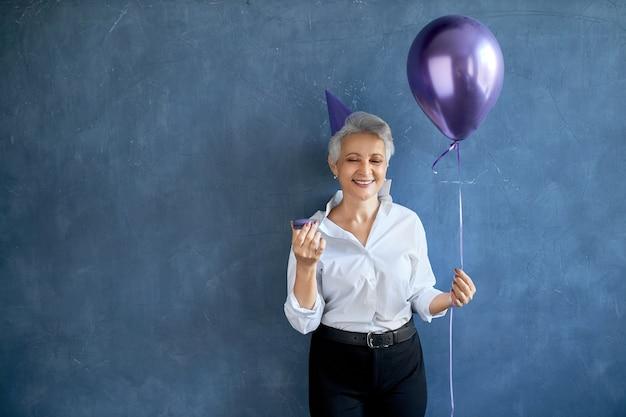 Porträt der positiven sorglosen reifen frau, die geburtstag feiert, glücklichen gesichtsausdruck habend, heliumballon und makrone haltend
