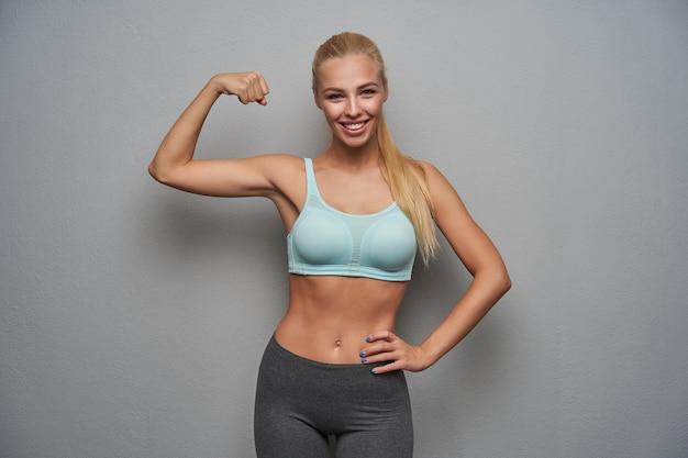 Porträt der positiven sportlichen langhaarigen blonden frau, die glücklich zur kamera schaut und ihre kraft mit erhobener hand zeigt, gekleidet in minzspitze und grauen leggins, während sie über hellgrauem hintergrund posiert