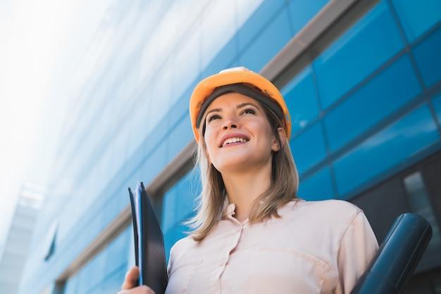 Porträt der professionellen architektenfrau, die gelben helm trägt und draußen steht. ingenieur- und architektenkonzept.