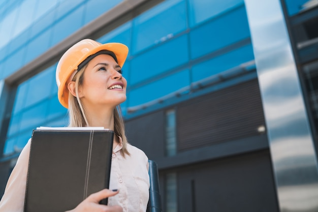 Porträt der professionellen architektenfrau, die gelben helm trägt und modernes gebäude im freien betrachtet. ingenieur- und architektenkonzept.