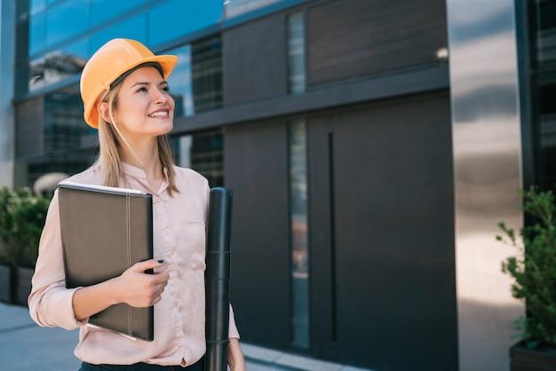 Porträt der professionellen architektenfrau, die gelben helm trägt und modernes gebäude im freien betrachtet