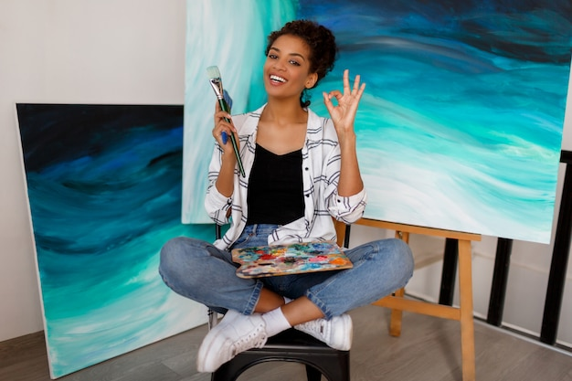 Porträt der professionellen künstlerin, die auf leinwand im studio malt. malerin an ihrem arbeitsplatz.