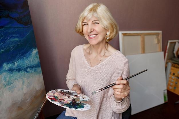 Porträt der professionellen künstlerin, die auf leinwand malt