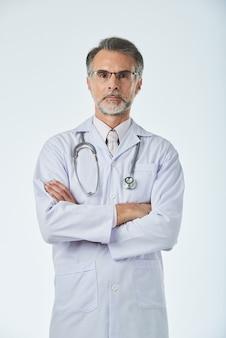 Porträt der professionellen medizinischen arbeitskraft, die für ein bild mit den armen gefaltet aufwirft