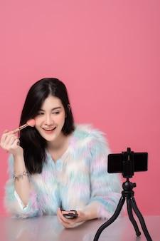 Porträt der professionellen schönheitslogger- oder bloggeraufzeichnung der jungen asiatischen frau, zum auf sozialen medien per smartphone auf stativ zu teilen.